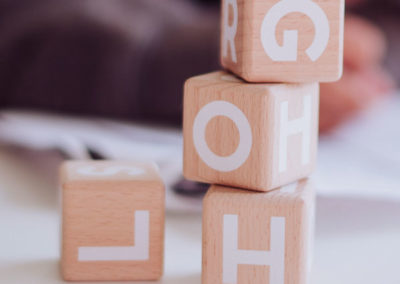 four wooden blocks with letters on each side